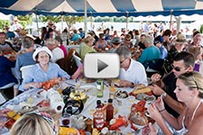 Photo of kettlebake guests eating clams, lobsters, chicken, sweet potatoes, and corn under the tent
