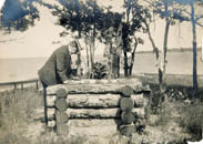 F.M.Smith standing at well on Cedar Island