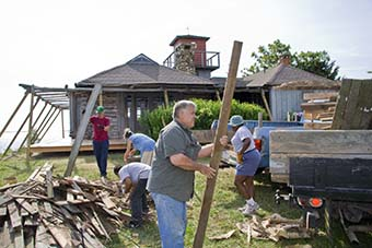 Volunteers clean debris from porch project